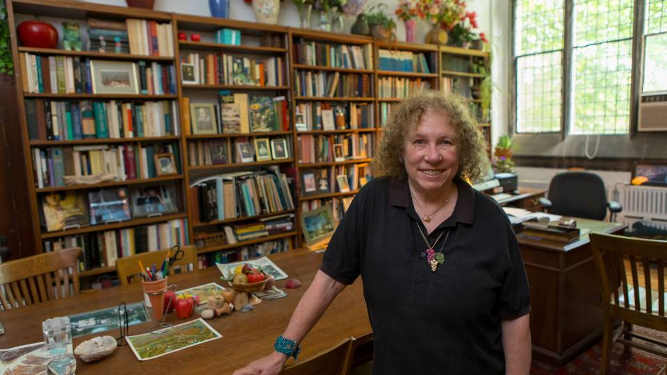 Susan Wolfson standing in her office surrounded by bookshelves