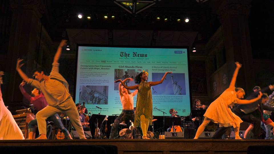 Students dancing on stage with orchestra and artwork projected on back screen