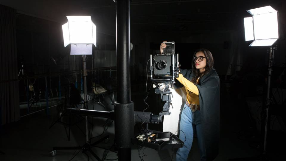 Angelica prepares large format camera in studio
