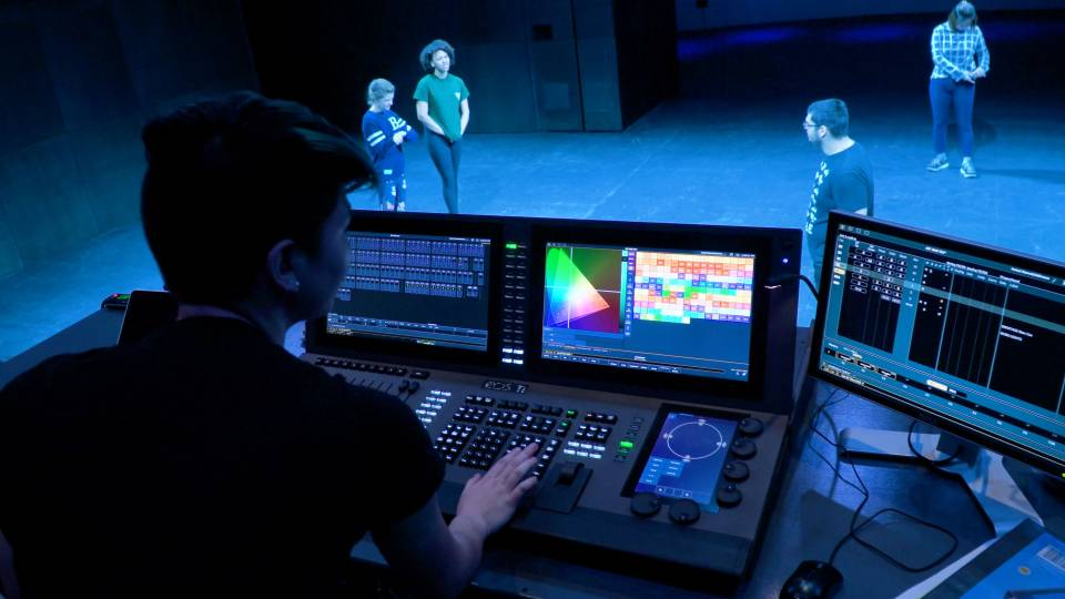 Student running lighting board with actors on stage