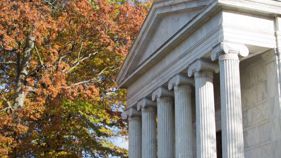 The columns of Whig Hall with autumn leaves in the background