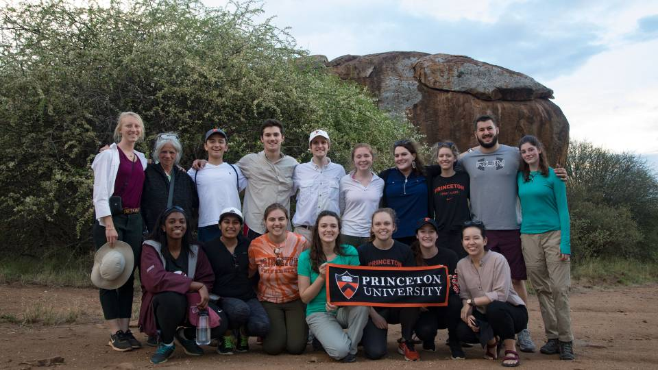 Students, faculty and researchers standing at base of Mt. Mukenya holding Princeton University banner
