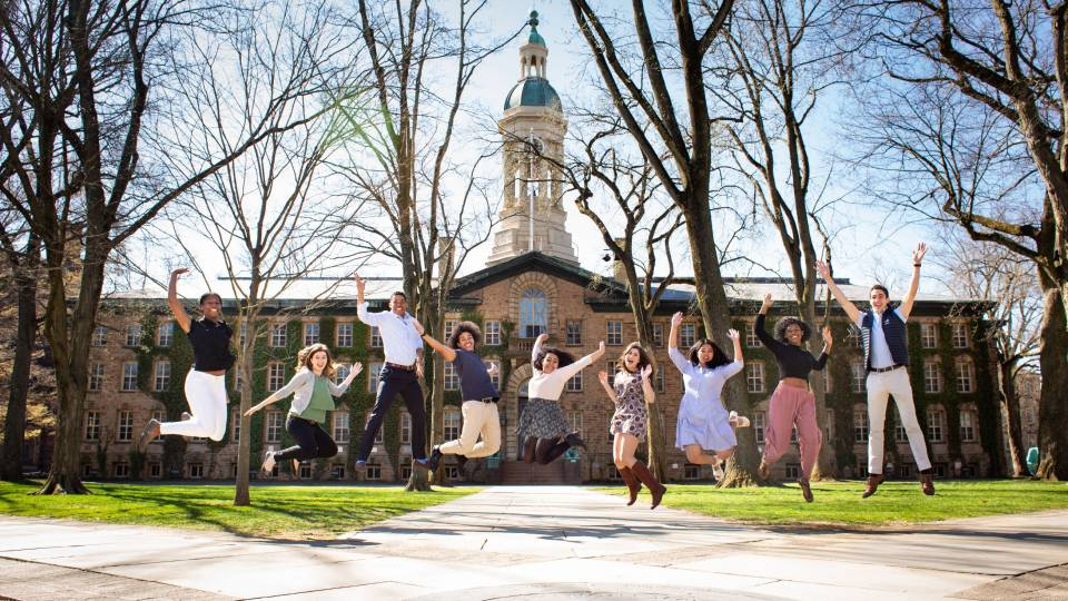 Maia Craver, Katie Tyler, Gaby Joseph, Jordan Thomas, Soraya Morales Nuñez, Allison Berger, Zoë Anne Toldedo, Christina Onianwa and Diego Negrón-Reichard leaping in the air in front of Nassau Hall