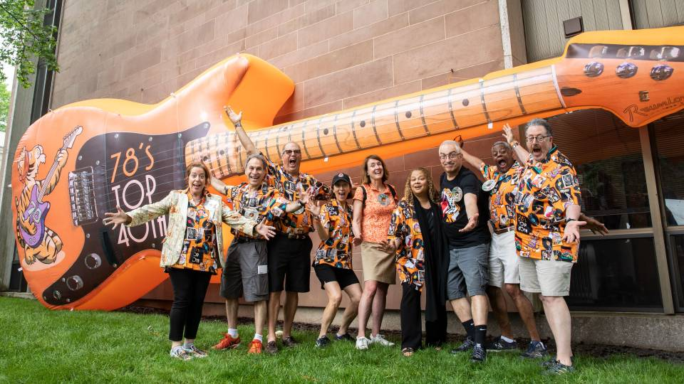 Members of Class of 1978 posing in front of giant balloon guitar