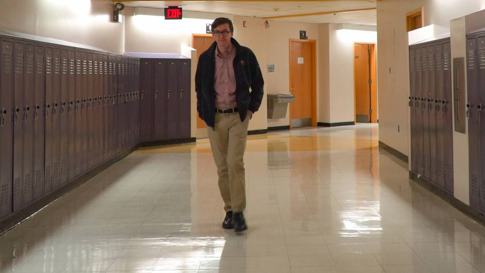 Tyler Simko walking down high school hallway