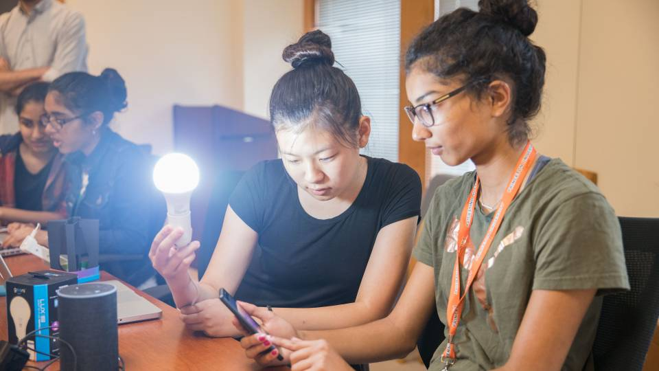 Students holding lit lightbulb while looking at cell phone