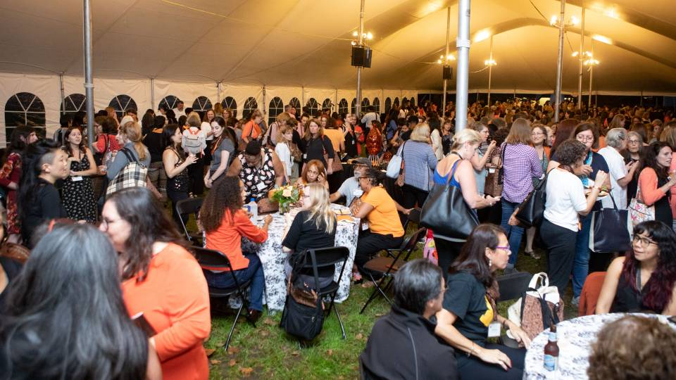Alumnae gathering under tent during opening reception