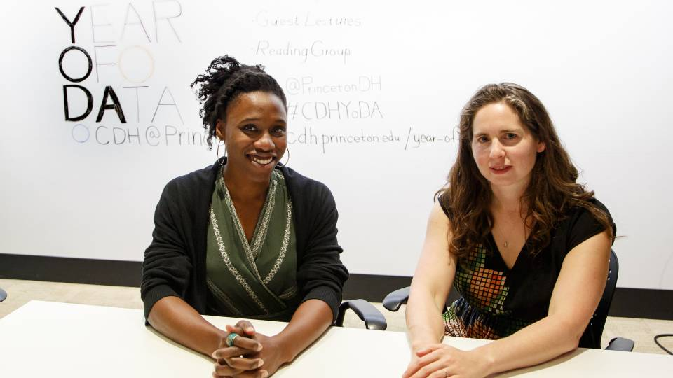 "Mimi Onuoha (left) and Lauren Klein sit at table with ""Year of Data "" on white board behind them"