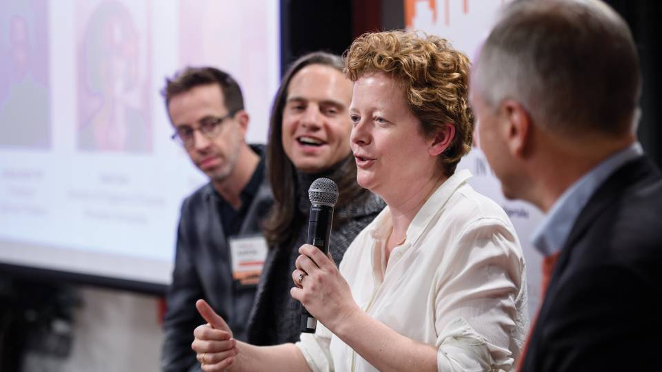 Jane Cox speaks into a microphone at TigerTalks 2018