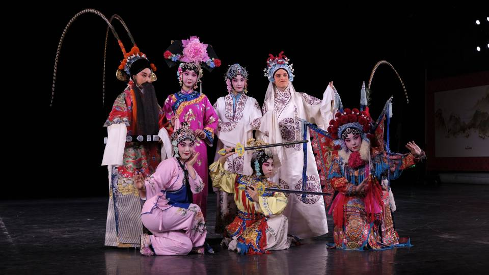 Students in Peking Opera costumes on stage