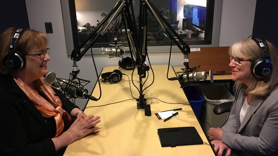 Patricia Falcone and Margaret Koval in studio booth recording podcast