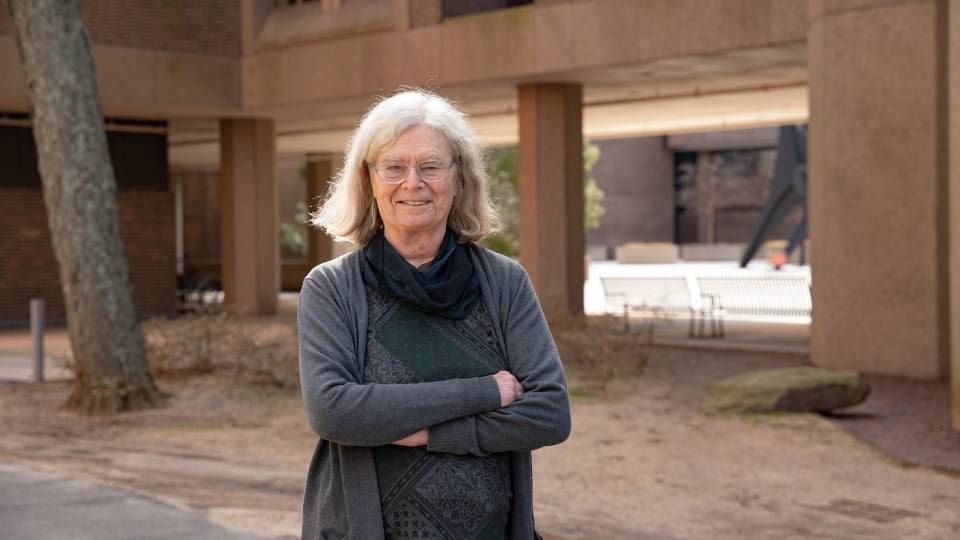 Karen Uhlenbeck poses in front of the math building