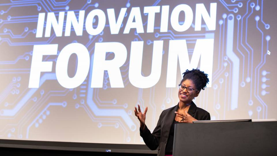 "Zakiya Smith Ellis speaking in front of a screen with the words ""Innovation Forum"" on it"