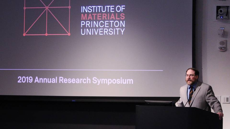 "Craig Arnold standing at podium in front of screen with the words ""Institute of Materials Princeton University 2019 Annual Research Symposium"""