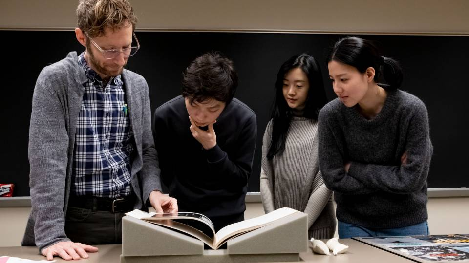 Franz Prichard standing with three students, looking at Japanese magazines
