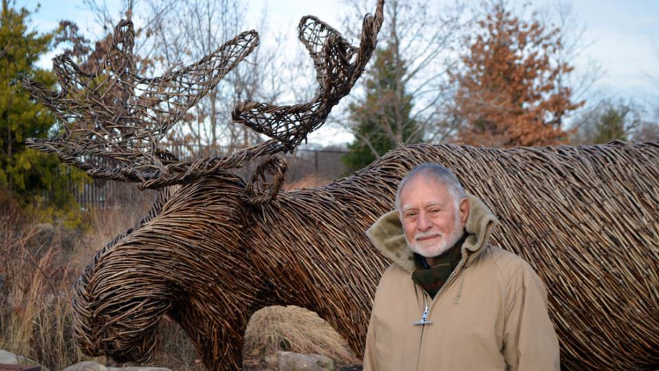 Robert Mark poses in front of a sculpture of a moose made of tree branches