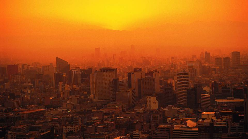 Orange tinted image of a city with sun and heat over it