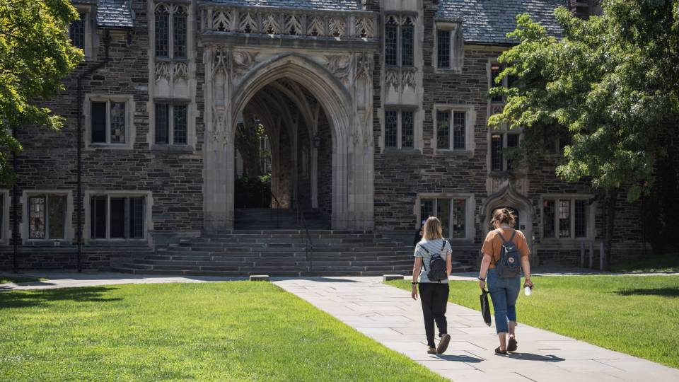 Two students walking toward an arch on campus