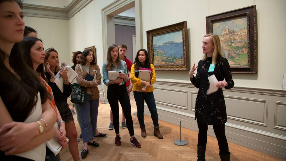 Bridget Alsdorf speaking with students in front of art