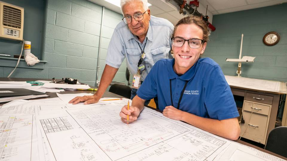 A technician and apprentice look over blueprint plans