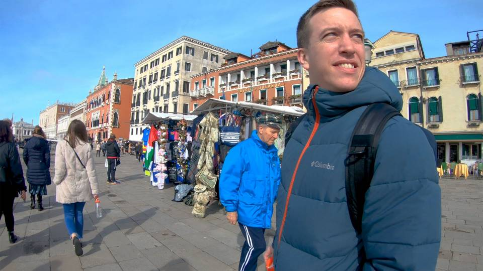 Kyle Masson looks over his shoulder on a sunny plaza in Venice, Italy