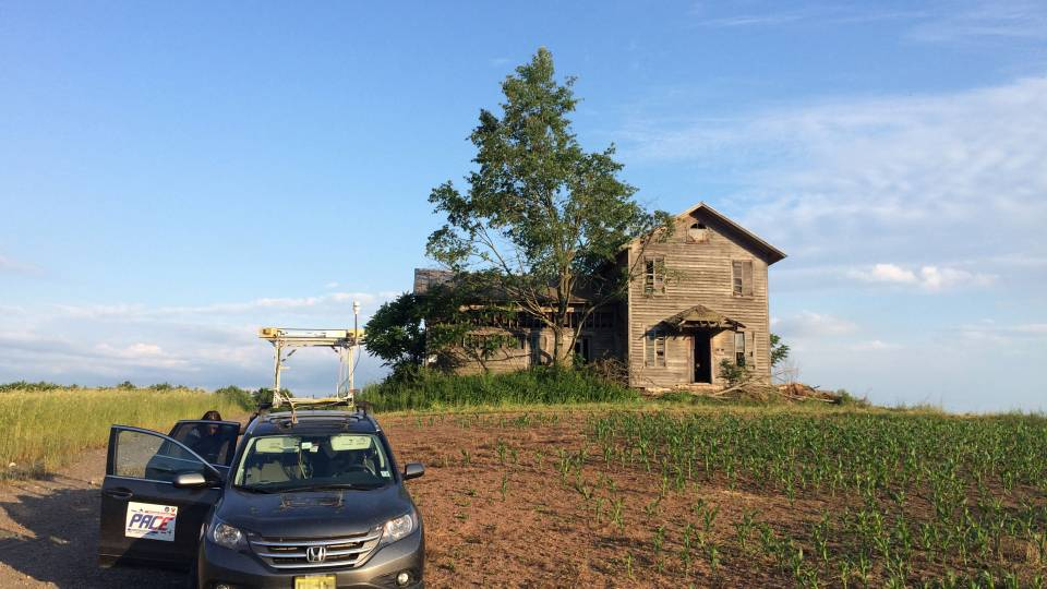 Mobile lab in front of farmhouse in a corn field