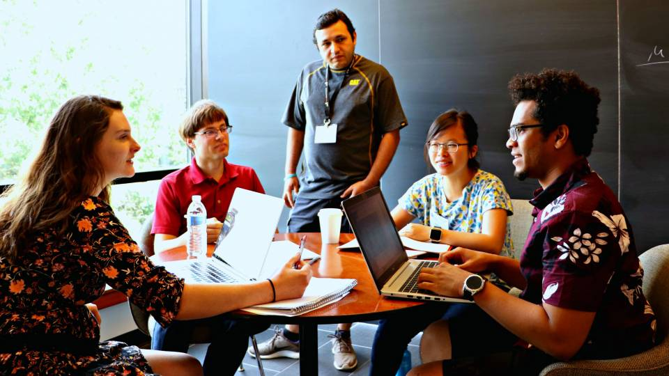 Students and researchers gather around a table