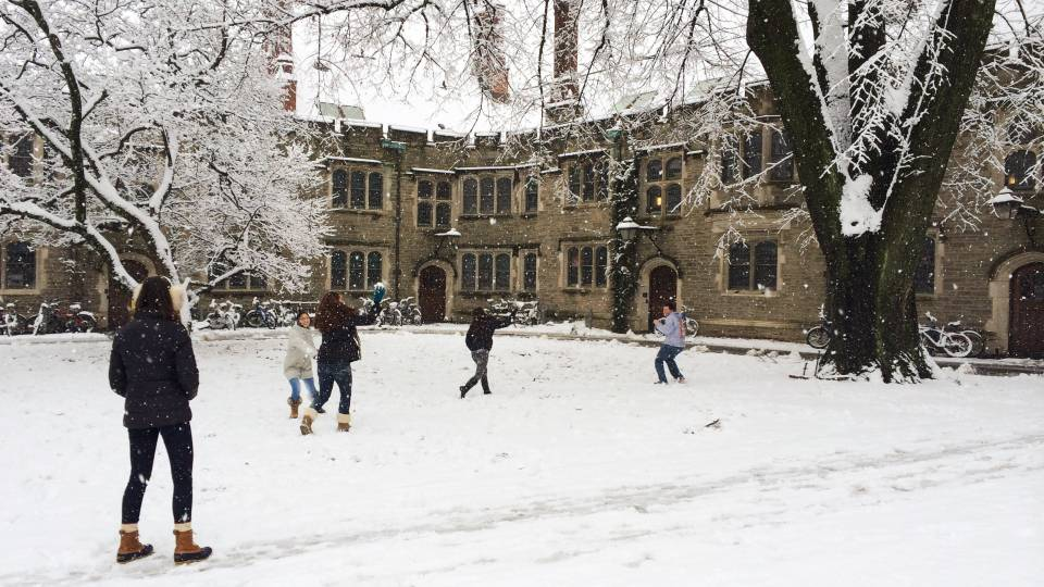 students play in the snow on campus