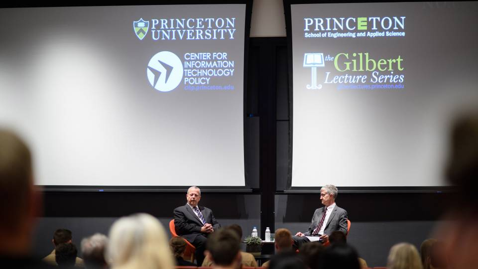 2 men on a stage with projections of Princeton University School of Engineering and Applied Science, CITP, Princeton University, and the Gilbert Lecture Series logos on a screen