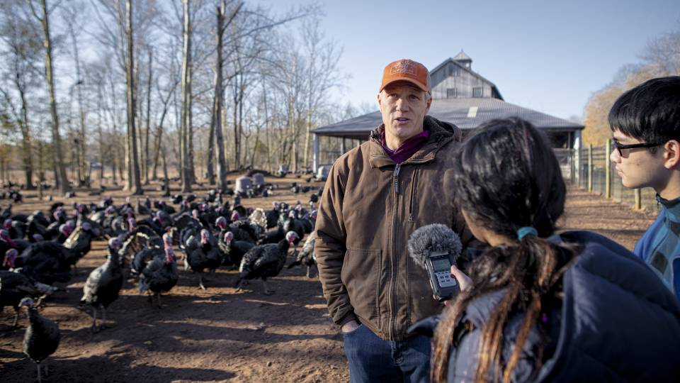 A farmer is interviewed by two students in front of his farm in Hopewell