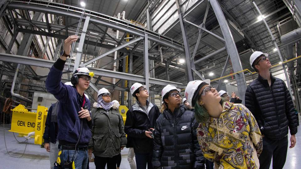 Students look up during a tour of a power plant
