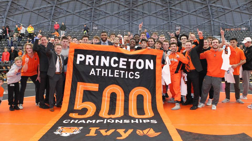 A group poses with a banner that reads, Princeton Athletics 500 Championships Ivy""