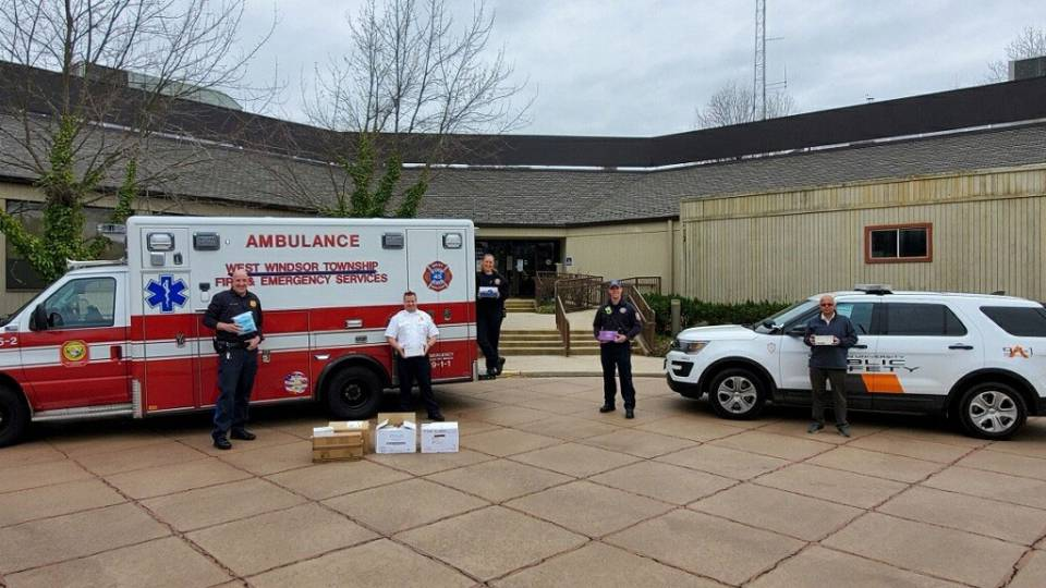 Staff pose with emergency vehicles and supplies in West Windsor