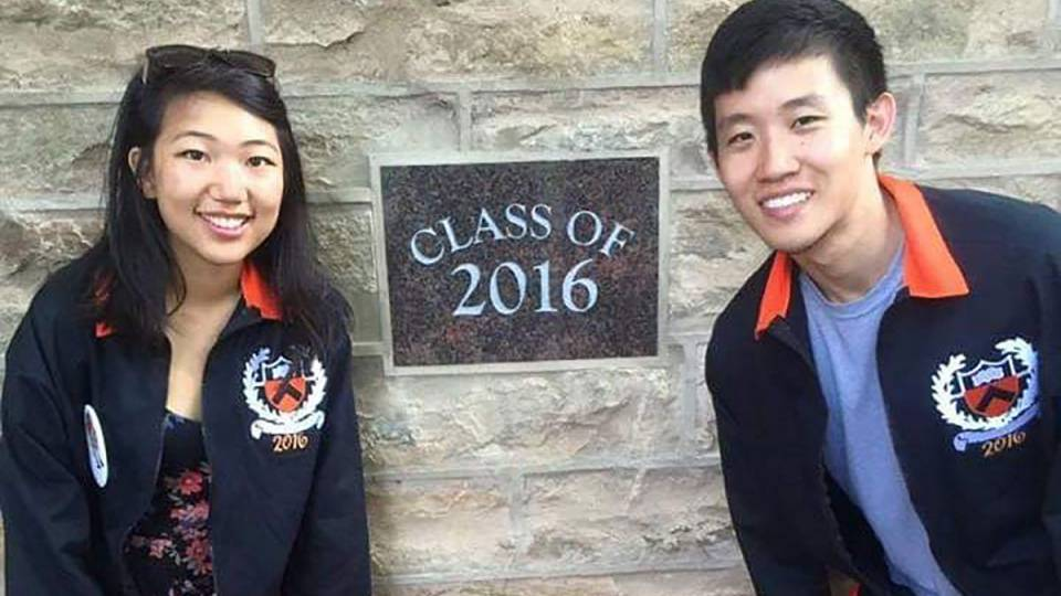 2 students pose in front of a Class of 2016 plaque