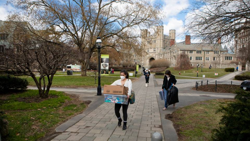 A student moves boxes of belongings onto campus