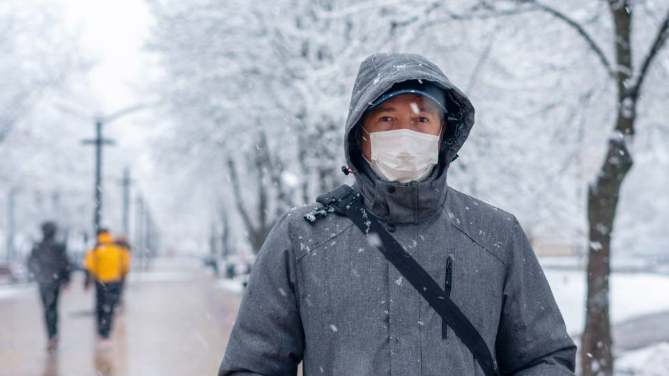 A masked person stands on a snowy walking path