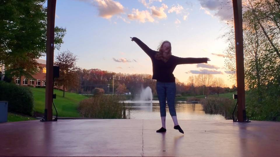 Video still of a dancer in front of a fountain in a pond at twilight
