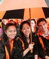 Seniors gather under a Tiger umbrella