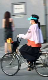 woman in mask on bicycle