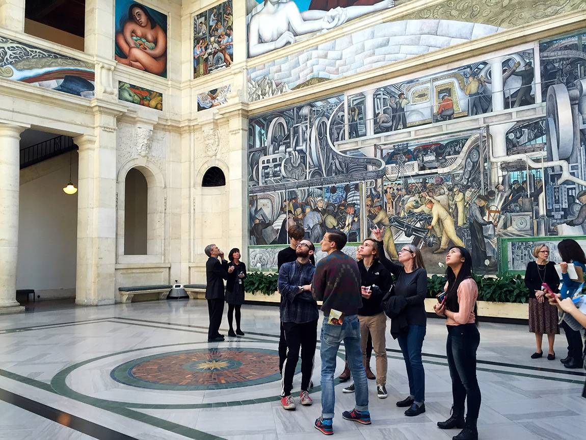 Professor Judith Hamera explains part of Diego Rivera's Detroit Industry fresco cycle to students during a visit to the Detroit Institute of Arts.