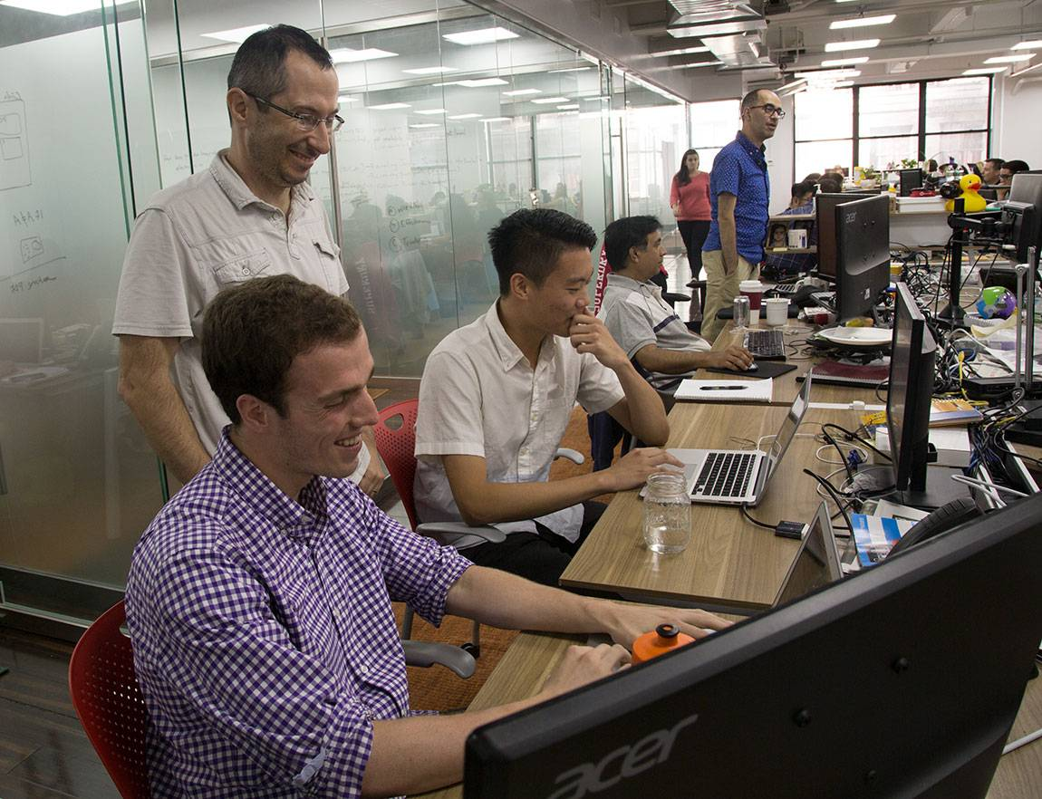 Princeton Start-Up Immersion Program juniors Raoul Rodriguez and Daniel Liu (seated left to right in foreground) work with Boris Boroda (standing), vice president of engineering at AbilTo