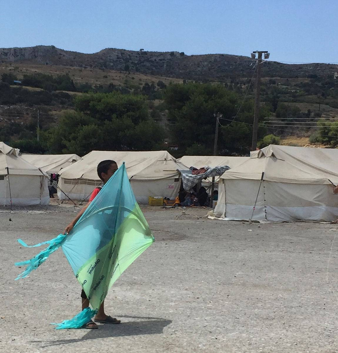 A Tale of Two Countries: Greece - boy with kite at Schisto camp