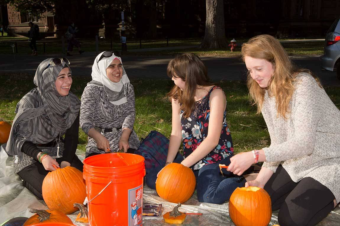 From left to right: Syrian refugees Rahaf and Reem get to know Princeton sophomores Stephanie Ward and Lilly Chadwick as they carve pumpkins on the lawn in front of Murray Dodge Hall.