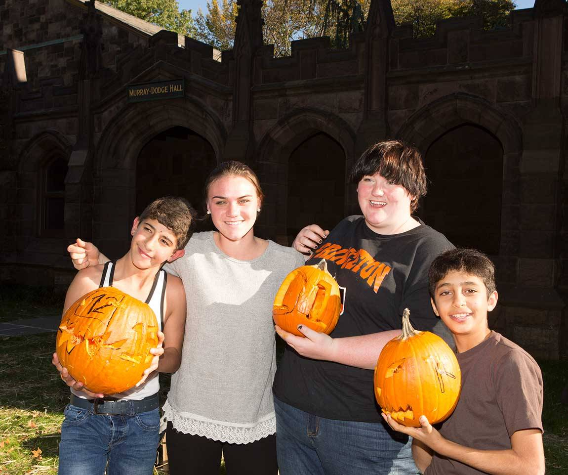 Princeton sophomores Carly Bonnet (center left) and Téa Wimer (center right) show off the pumpkins they carved with Abdulhafiz (far left) and Khaled (far right).