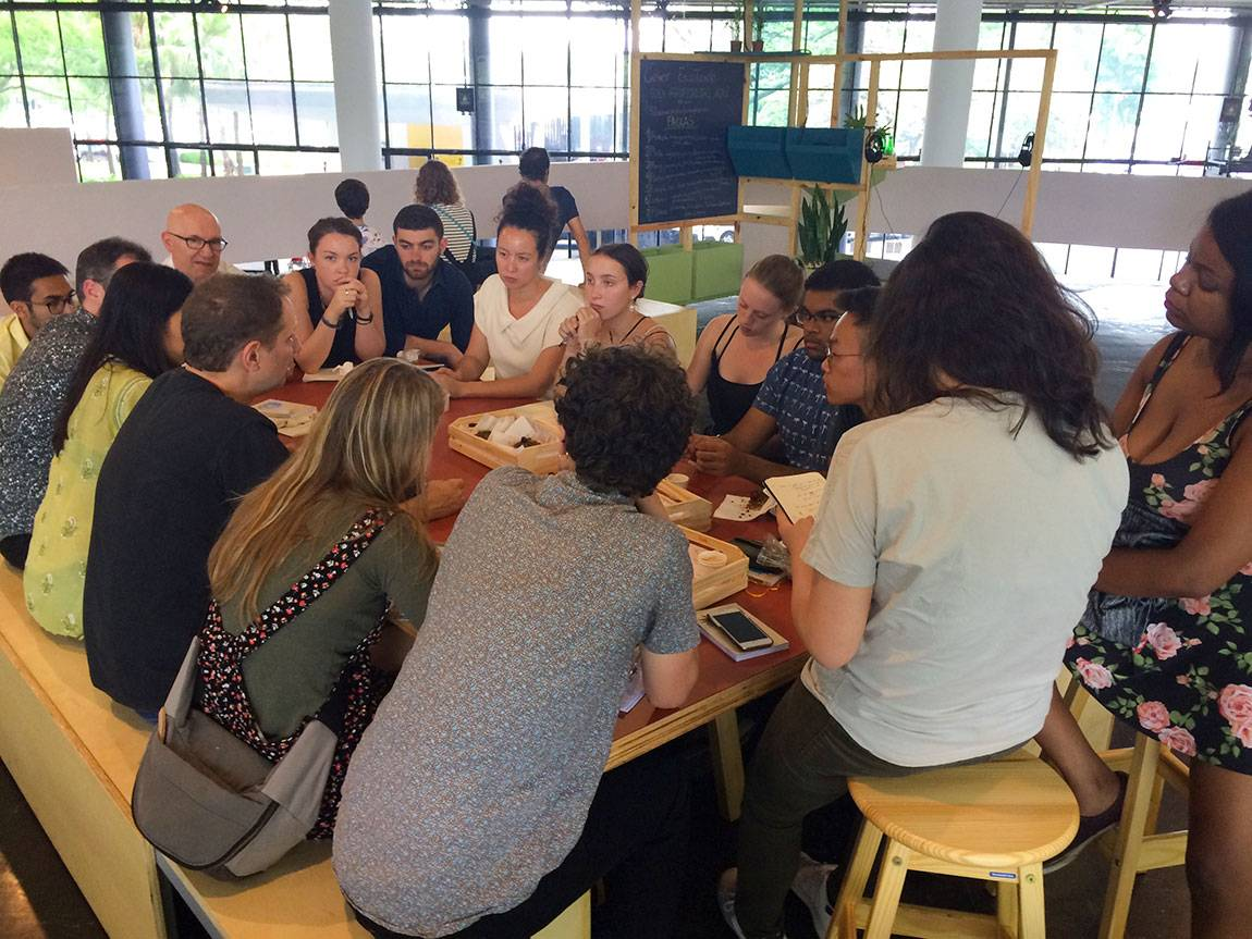 Sitting inside of the 32nd São Paulo Bienal with head curator Jochen Volz (seated on left bench, in black shirt)