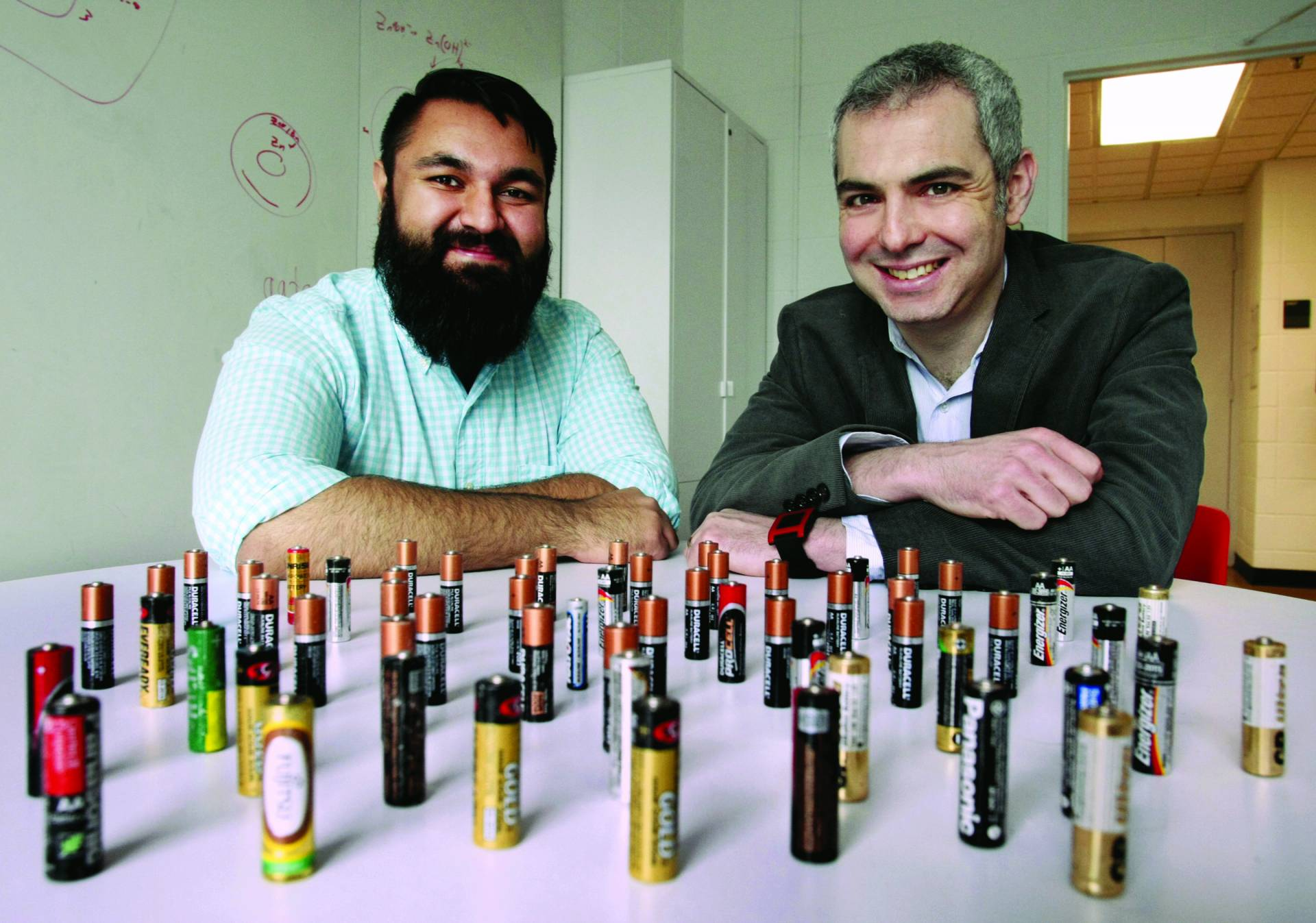 Photo showing two Princeton University researchers sitting at a table on which are displayed AA batteries that they use in their research.