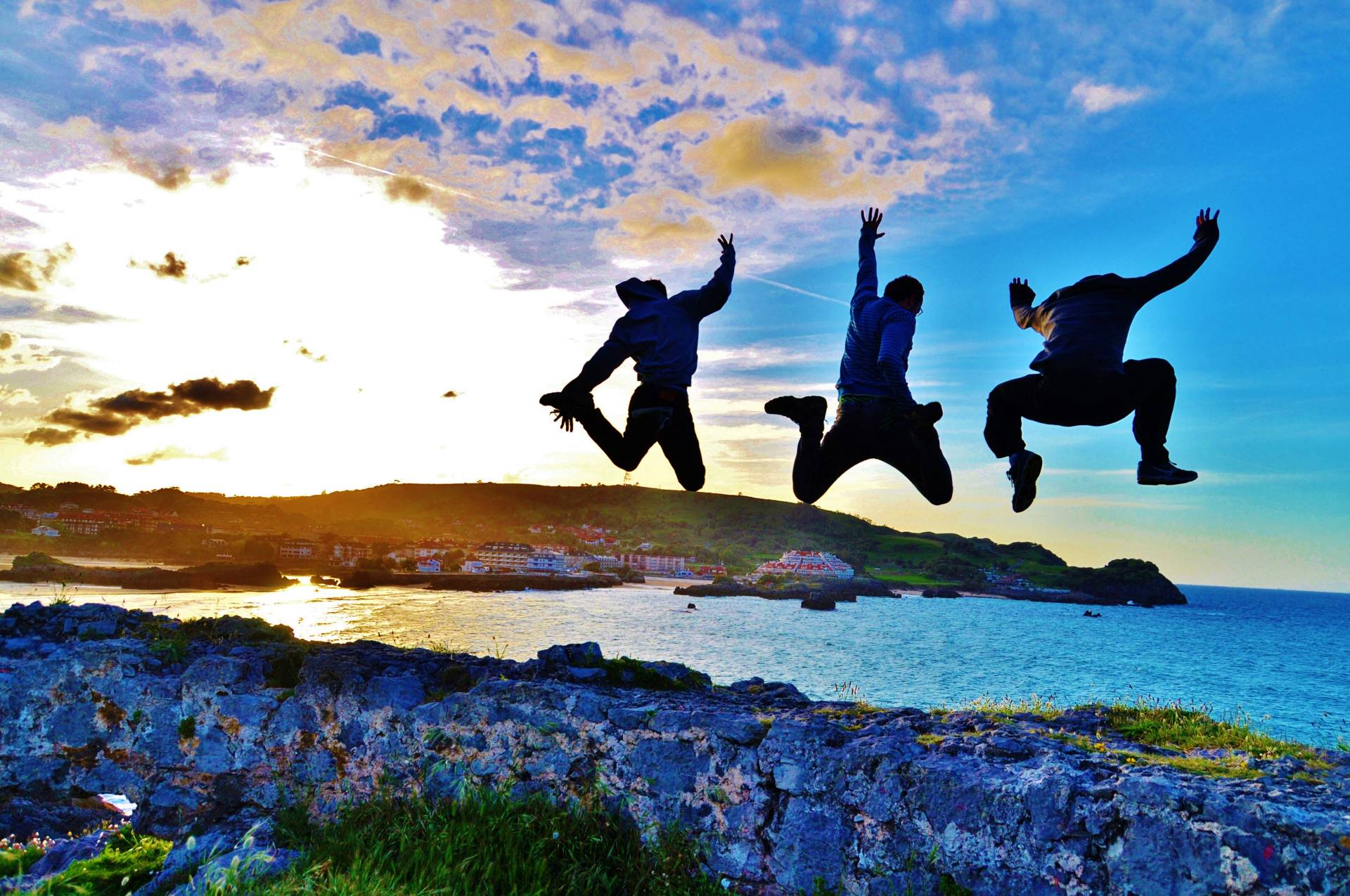 Students jumping during sunset near a lake while travelling abroad