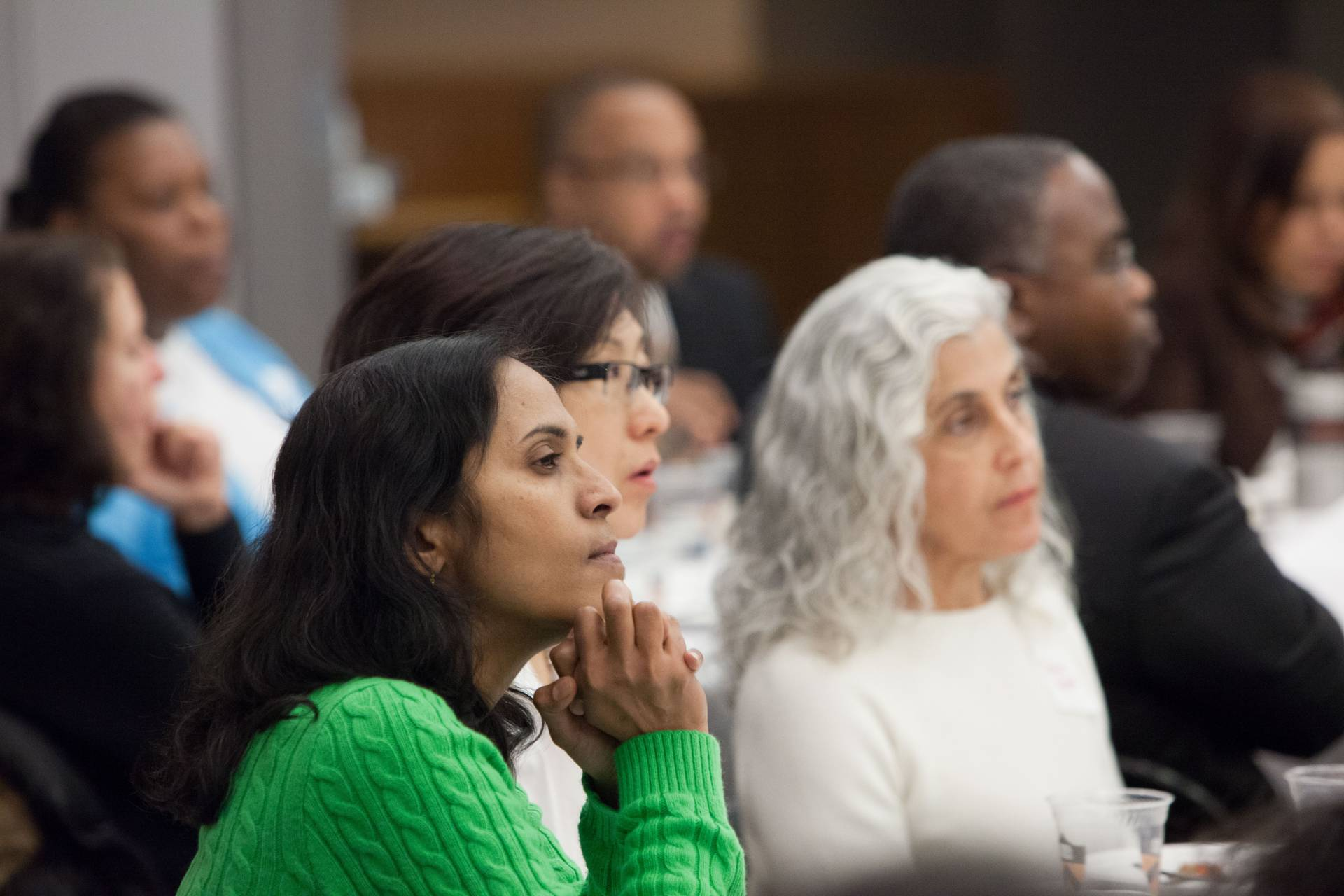 University staff members listen to a speaker at an Employee Resource Group meeting.
