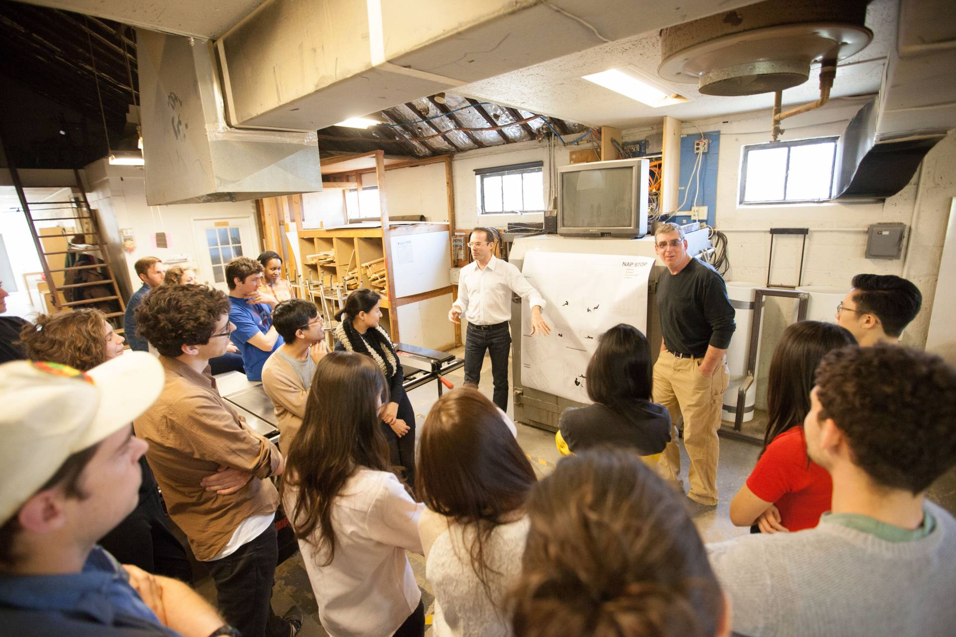 A class is held in an architecture workshop, with students huddled around two professors.