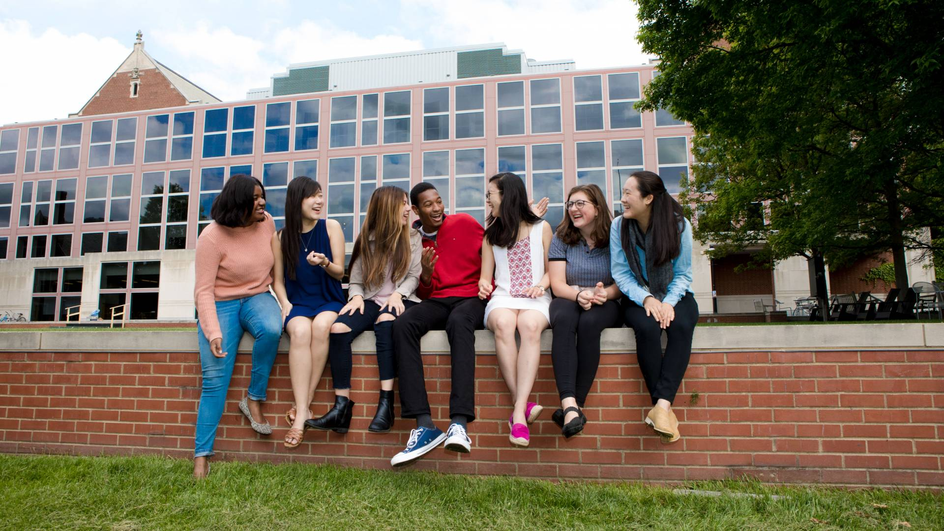 Jin Yun Chow and friends sitting on wall behind Frist Campus Center